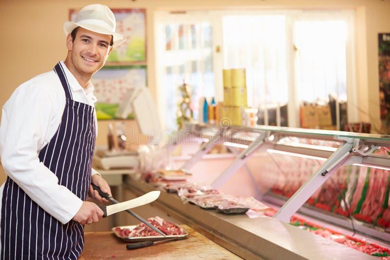 Slaktaren Preparing Meat In shoppar arkivbild