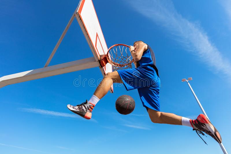 Slam Dunk. Side view of young basketball player making slam dunk.  stock photo