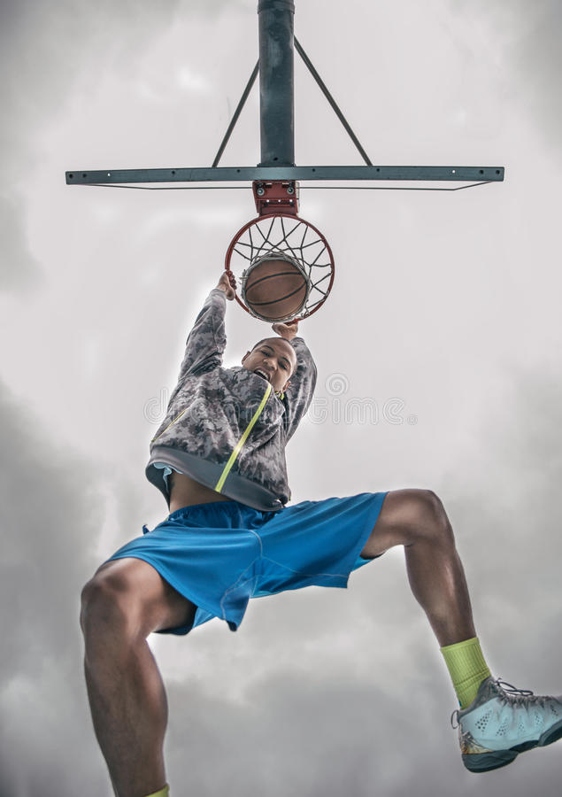 Slam dunk. Sportive man hanging from the basket and looking down triumphant at camera after a slam dunk - Basketball player sroring for his team stock image