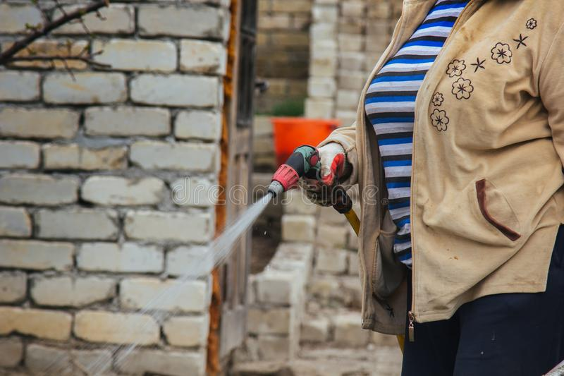 Slang för vatten för kvinnainnehavträdgård som bär färgrika wellies som bevattnar trädgården royaltyfri fotografi
