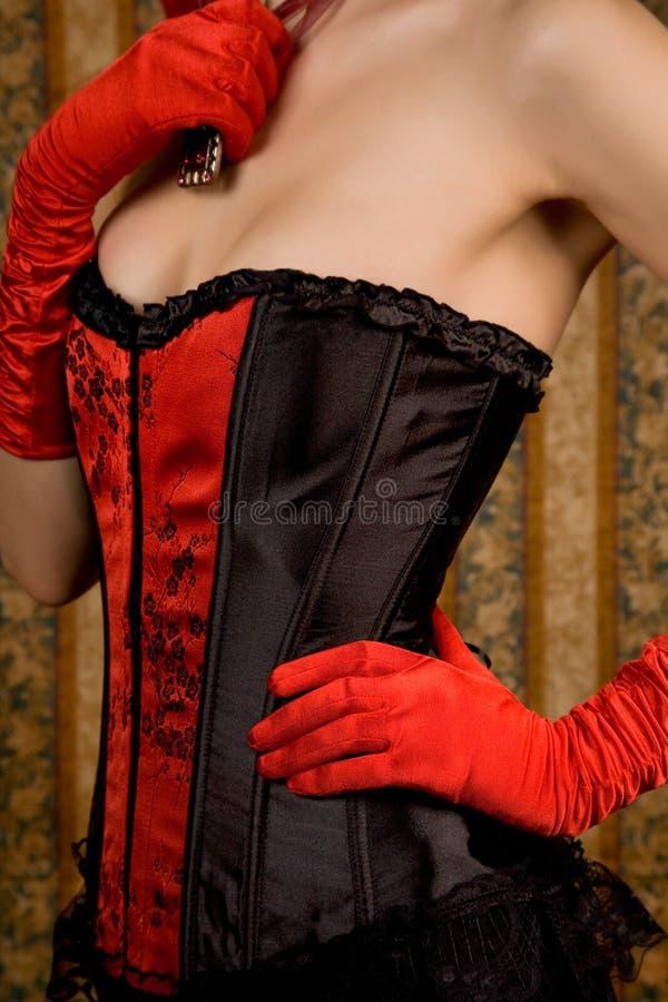 slank övre kvinna för tät korsettred royaltyfri bild