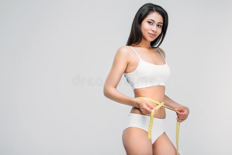 slank afrikansk amerikanflicka i underkläder som mäter hennes midja royaltyfri bild