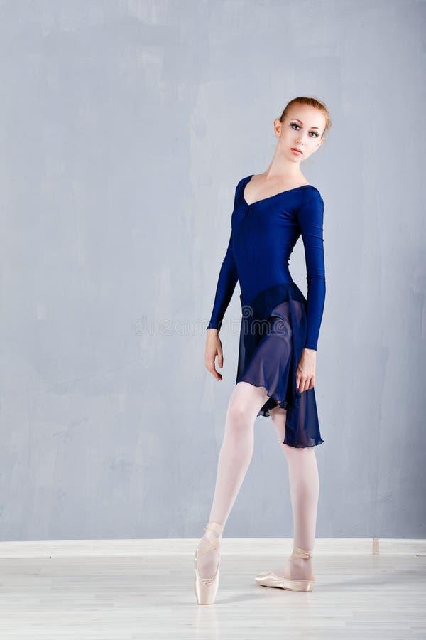 Slank ballerina i en blå klänningdans arkivbild