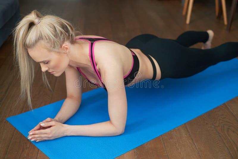 Slank blond flicka för idrottsman nen för ung kvinna för kondition som hemma gör plankaövning på mattt royaltyfri bild