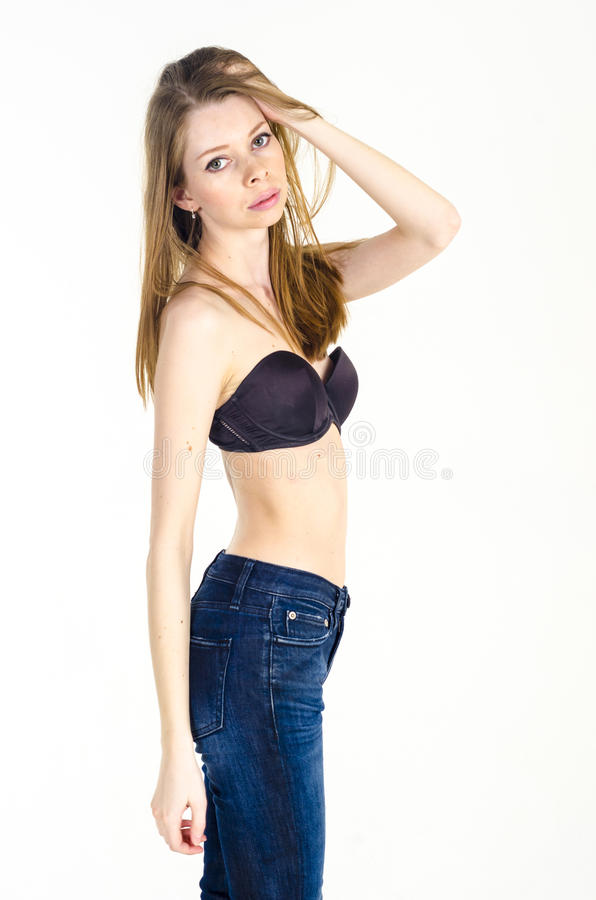 Slank blond flicka med långt hår i jeans och svart behå royaltyfria bilder
