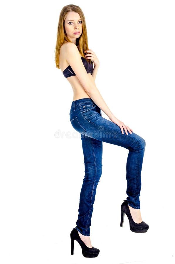 Slank blond flicka med långt hår i jeans och svart behå royaltyfri foto
