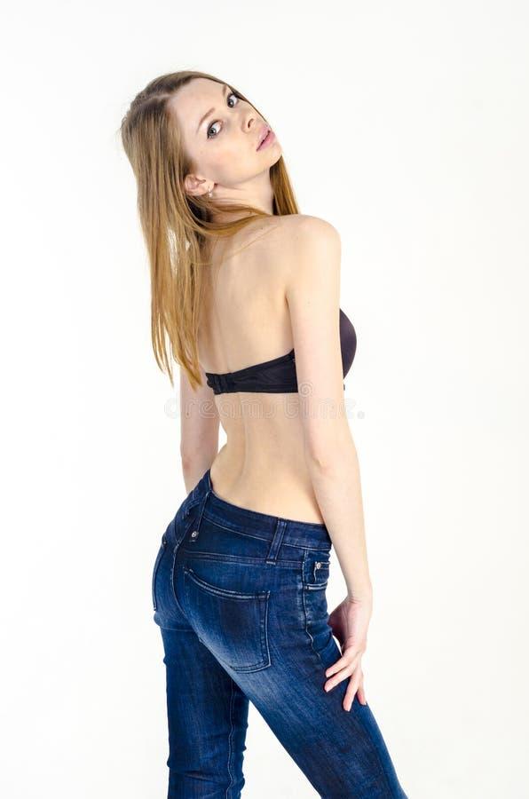 Slank blondemeisje met lang haar in jeans en zwarte bustehouder stock fotografie