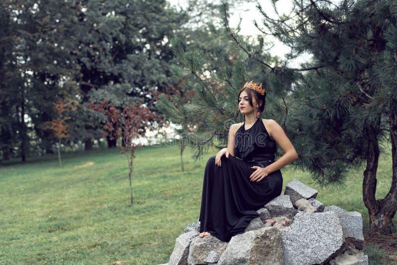 Slank brunette in een zwarte kleding in het park royalty-vrije stock foto's