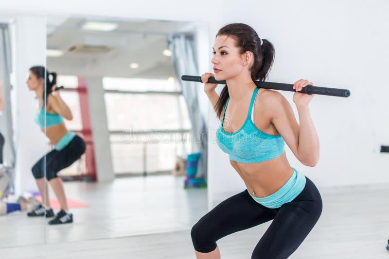 Slank brunettkvinna som gör squats med skivstången i konditionkorridor royaltyfri foto