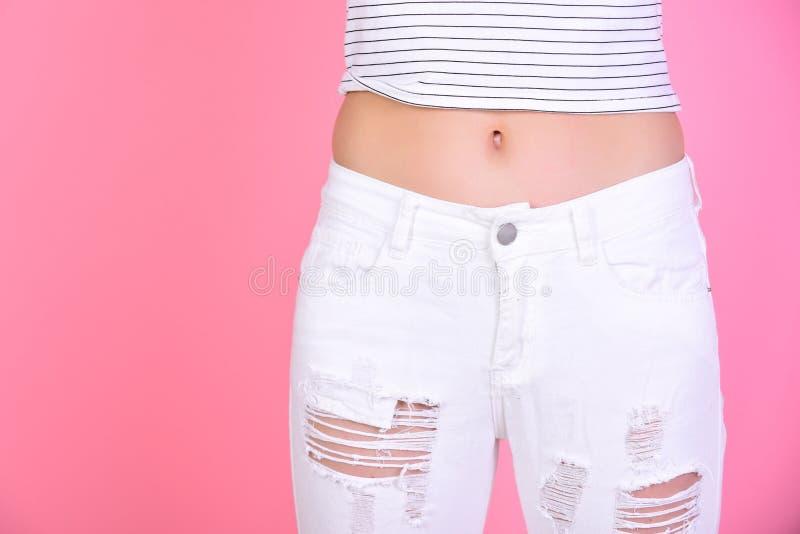 Slank buk av kvinnan i vit jeans på rosa bakgrund, kopieringsutrymme banta och konditionbegreppsshower gör perfekt kroppen Kvinna arkivbild