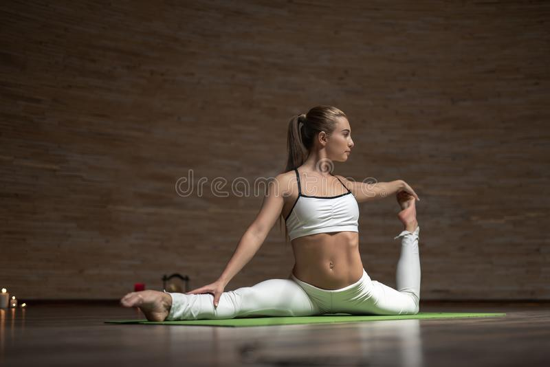 Slank dam som trycker på hennes tår, medan sträcka hennes ben på matt yoga royaltyfri bild