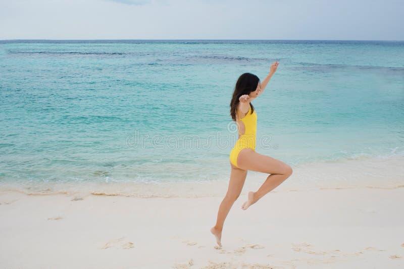 Slank donkerbruin meisje die in geel zwempak op het strand springen stock afbeeldingen