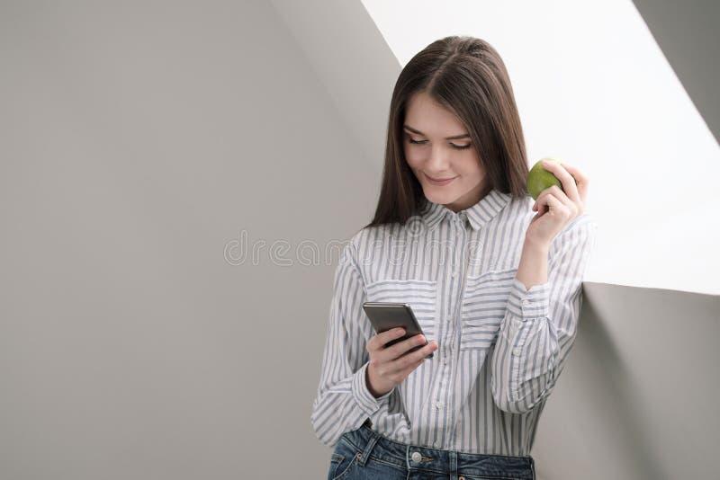 Slank donkerbruin meisje met lang haar op een witte achtergrond dichtbij het bureauvenster Gebruikt een smartphone en het babbele royalty-vrije stock fotografie