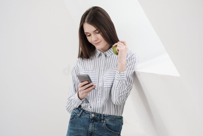 Slank donkerbruin meisje met lang haar op een witte achtergrond dichtbij het bureauvenster Gebruikt een smartphone en het babbele royalty-vrije stock foto's
