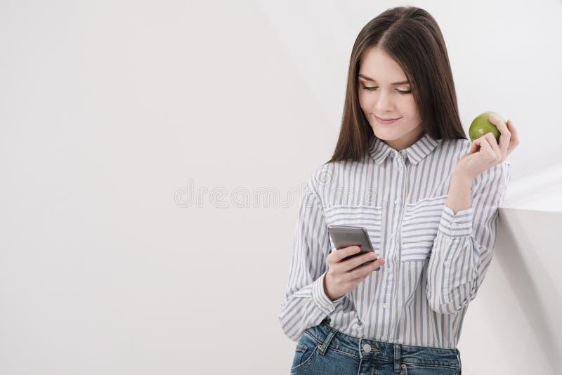 Slank donkerbruin meisje met lang haar op een witte achtergrond dichtbij het bureauvenster Gebruikt een smartphone en het babbele royalty-vrije stock afbeeldingen