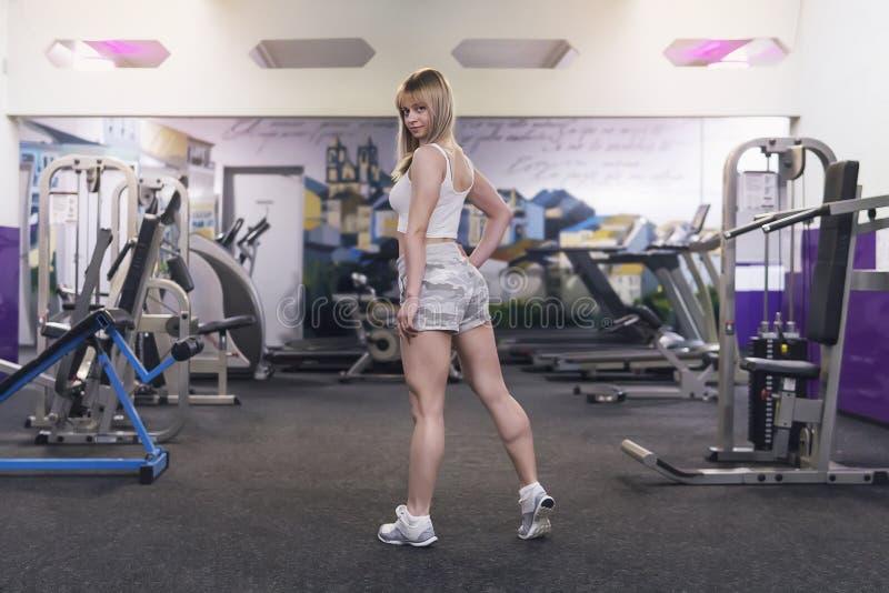 Slank en aantrekkelijk vrouwelijk model met lang blondehaar gekleed in witte t-shirt, de tribunes van camouflageborrels Schittere royalty-vrije stock fotografie