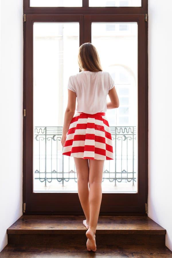 Slank flicka i den korta kjolen som ut går till balkongen royaltyfri foto