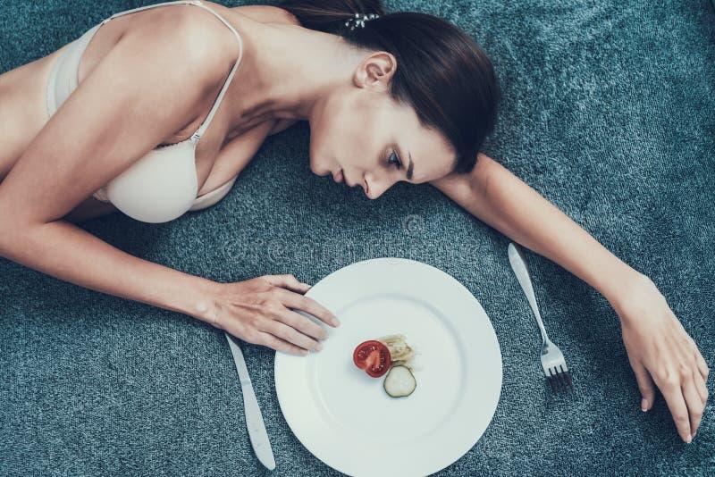 Slank flicka med anorexi som ligger på soffan med plattan royaltyfria bilder