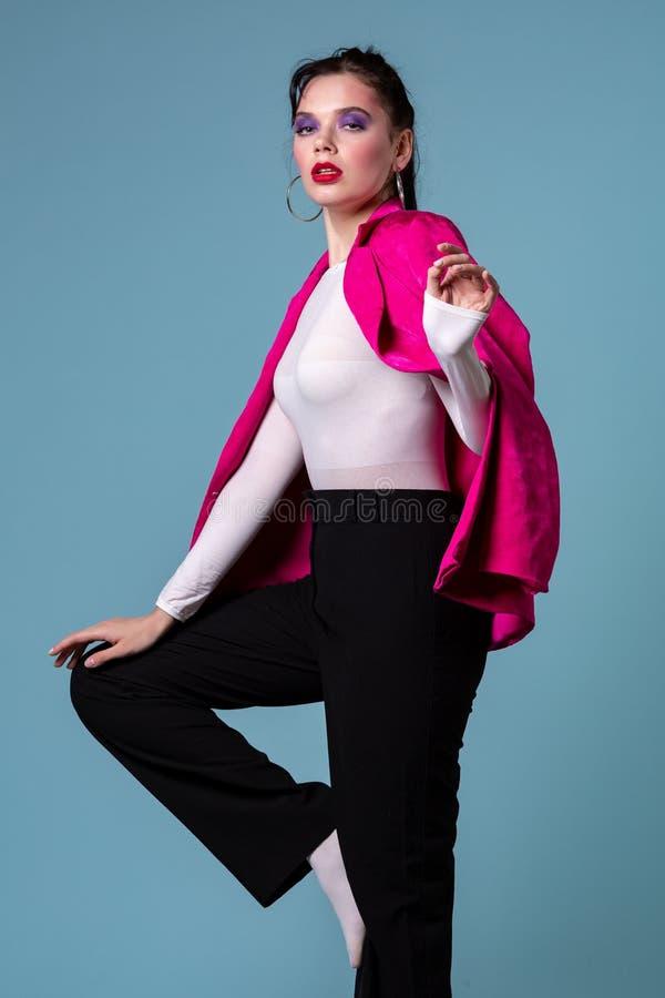 Slank glamorös dam som poserar i studio med allvarligt framsidauttryck arkivfoto