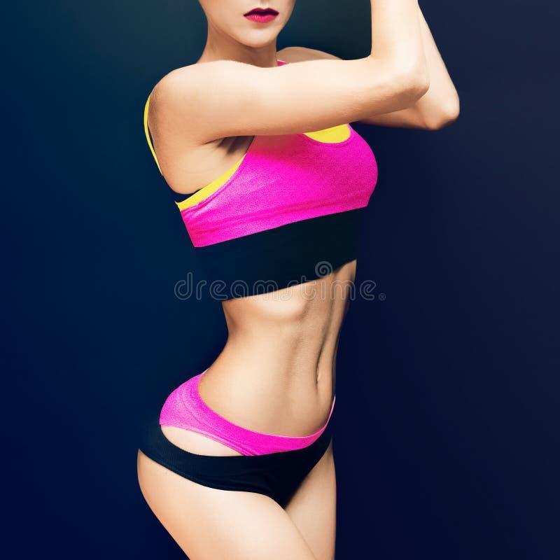 Slank idrotts- konditionflicka på en svart bakgrund i modeet royaltyfria foton