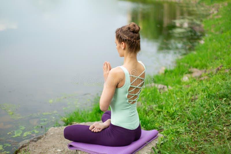 Slank Kaukasisch donkerbruin meisje die yoga in de zomer op een groen gazon doen door de rivier royalty-vrije stock afbeelding