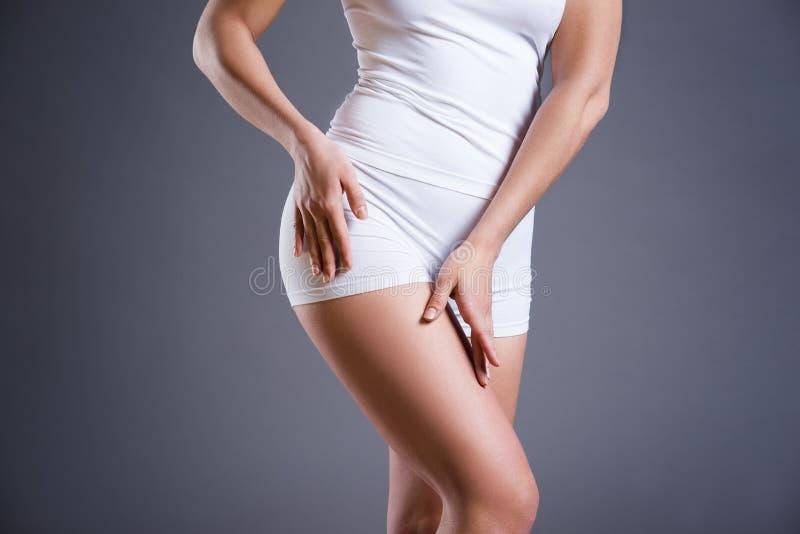 Slank kvinna i den vita underkläderna på grå studiobakgrund, perfekt kvinnlig kropp arkivfoto