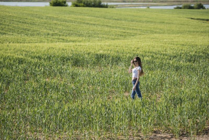 Slank kvinna i grönt fält arkivfoto