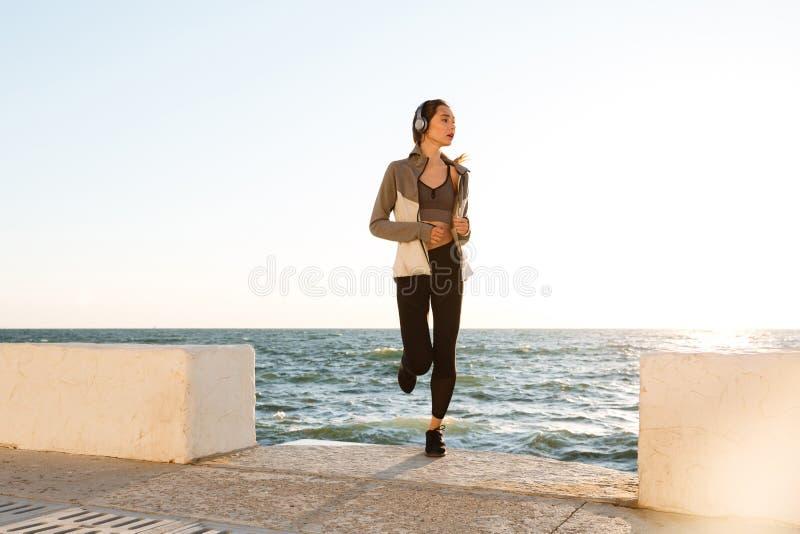 Slank kvinna med perfekt kroppspring på sjösidan arkivfoton