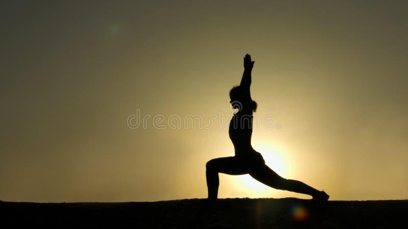 Slank kvinna som håller jämvikt som gör yoga mot den stora inställningssolen, meditation arkivfoto