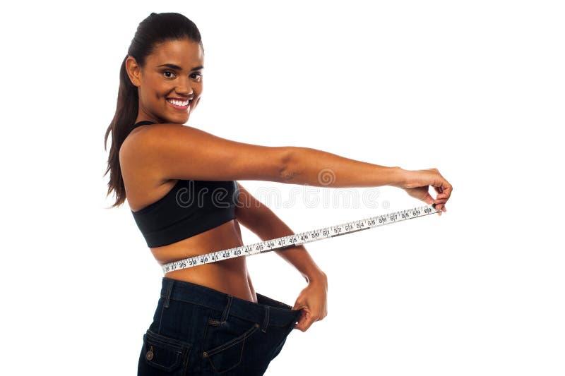Slank kvinna som mäter hennes midja arkivfoton