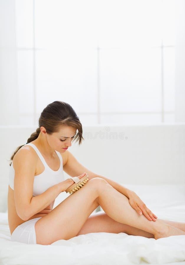 Slank kvinna som sitter på underlag och gör benmassage arkivbild