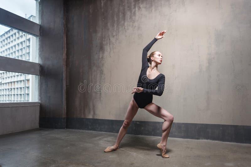 Slank kvinnadans för plasticitet nära fönstret fotografering för bildbyråer
