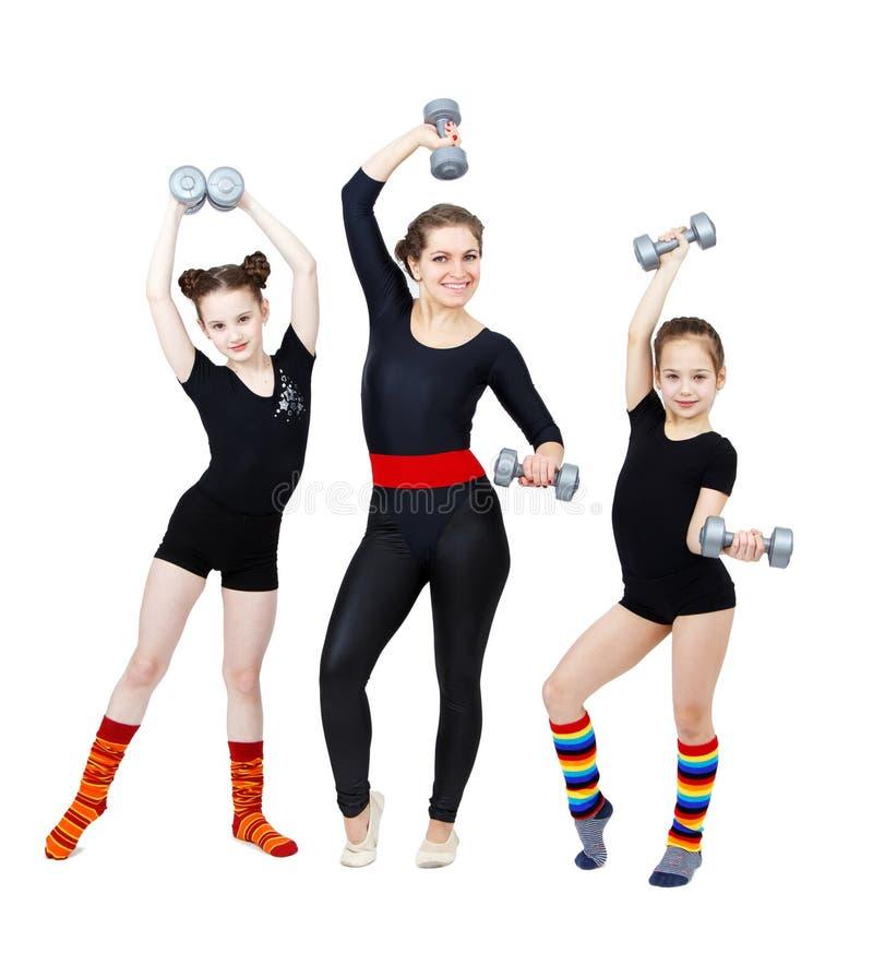Slank kvinnlig konditioninstruktör och två flickagymnaster arkivbild