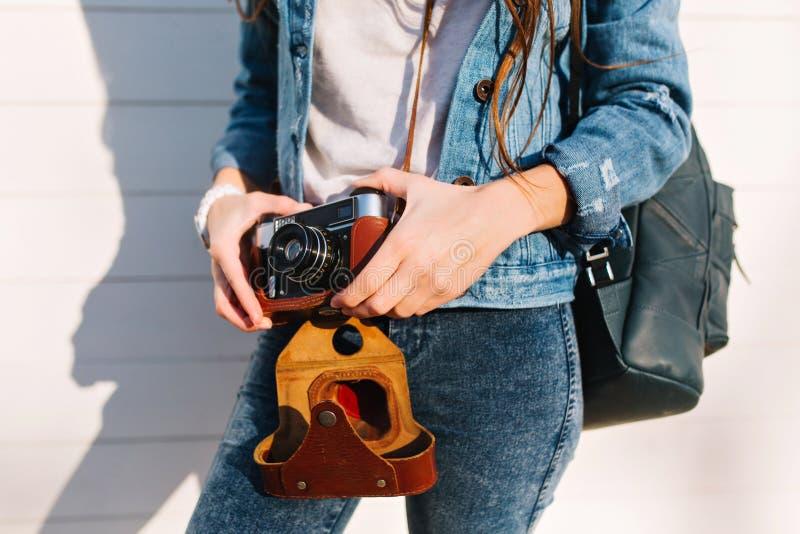 Slank langharig modieus meisje die in in denimuitrusting en wit polshorloge retro camera houden Jong wijfje royalty-vrije stock afbeelding