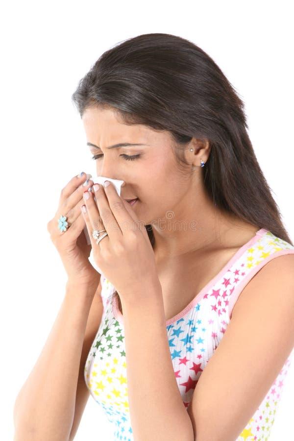 Slank meisje dat met papieren zakdoekje niest stock foto