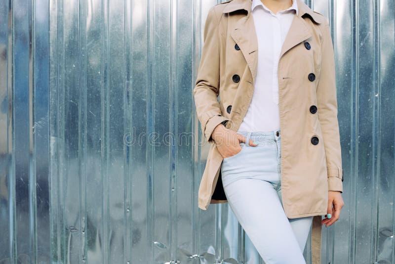 Slank meisje in jeans, een beige laag en een wit overhemd in openlucht in de lente royalty-vrije stock afbeeldingen