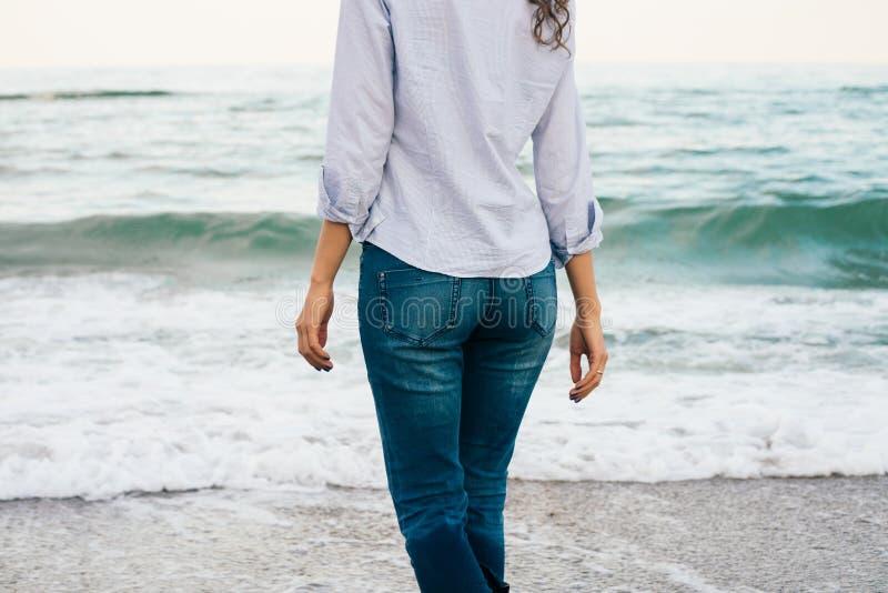 Slank meisje in overhemd en jeans die langs het strand lopen Mening Fr stock foto