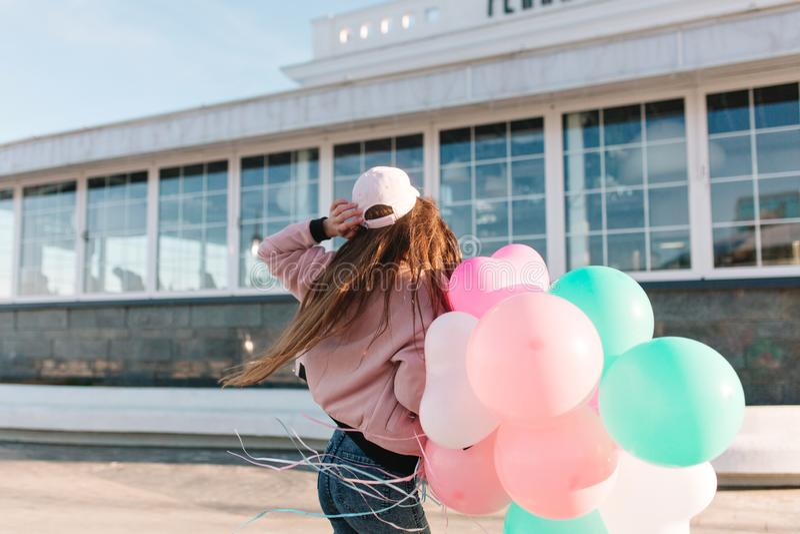 Slank modieus meisje die in roze GLB buiten in ochtend dansen terwijl wind die met haar lang donker haar spelen In brunette stock fotografie