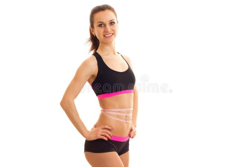 Slank mooi meisje in sportenbovenkant die en voor de camera glimlachen stellen stock fotografie