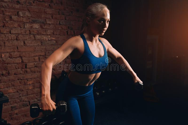 Slank muskulös blond kvinna som gör övningar för abdorminalmuskler royaltyfria foton