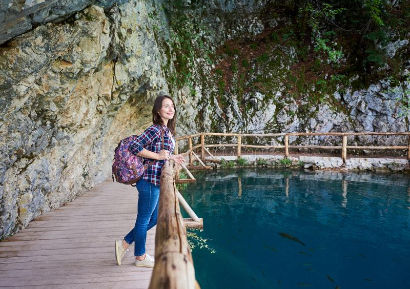 Slank nätt le turist- flicka med ryggsäckanseende på träbana royaltyfria bilder