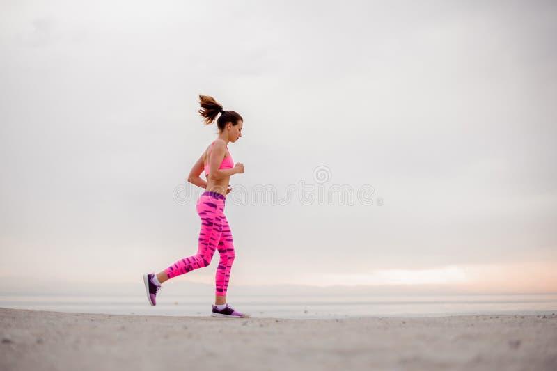 Slank och ung kvinna som kör över sjösidan i morgonen arkivfoto