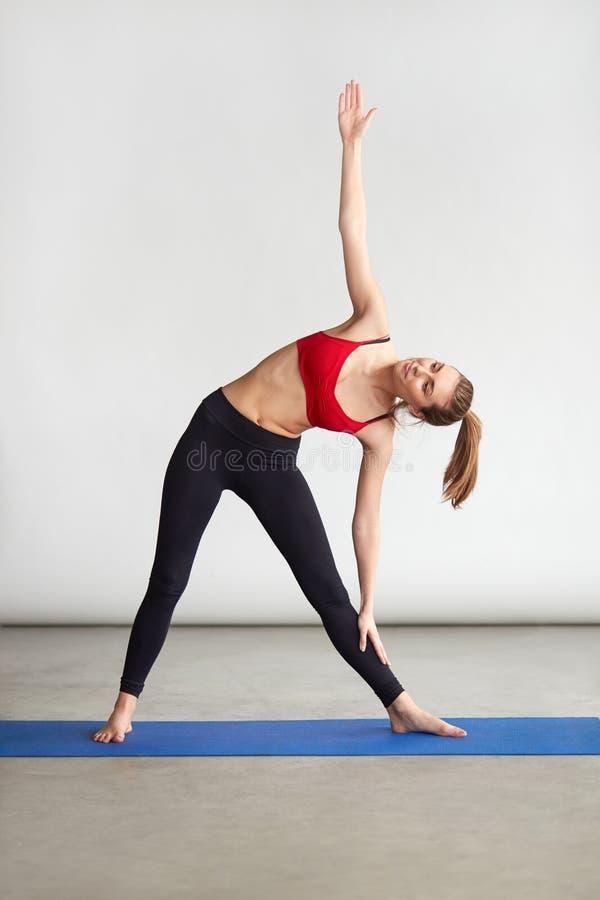 Slank sportief meisje die Driehoeksyoga doen stock foto's