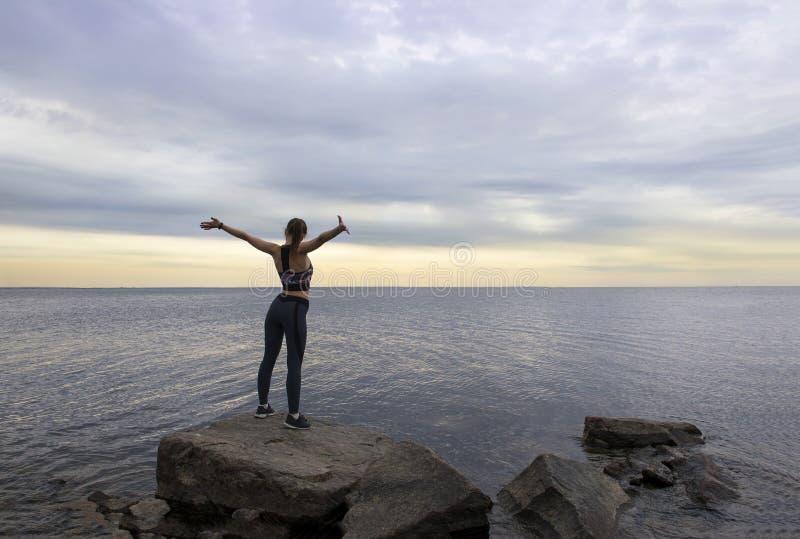 Slank sportig flicka i sportkläder som står på en sten på stranden med armar som är utsträckta på solnedgången, sikten från baksi royaltyfria foton