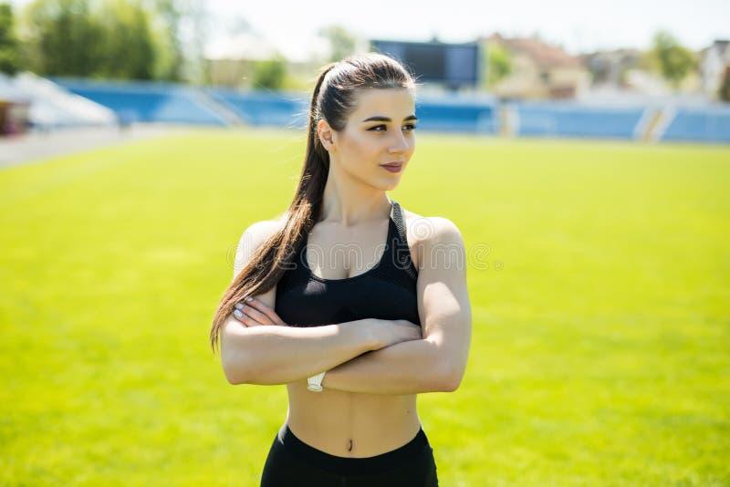 Slank sportkvinna Att le sportkvinnaanseende med armar vek på stadion arkivbild
