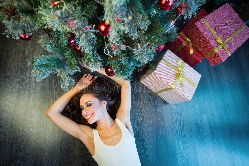 Slank ung flicka nära julgranen royaltyfri foto