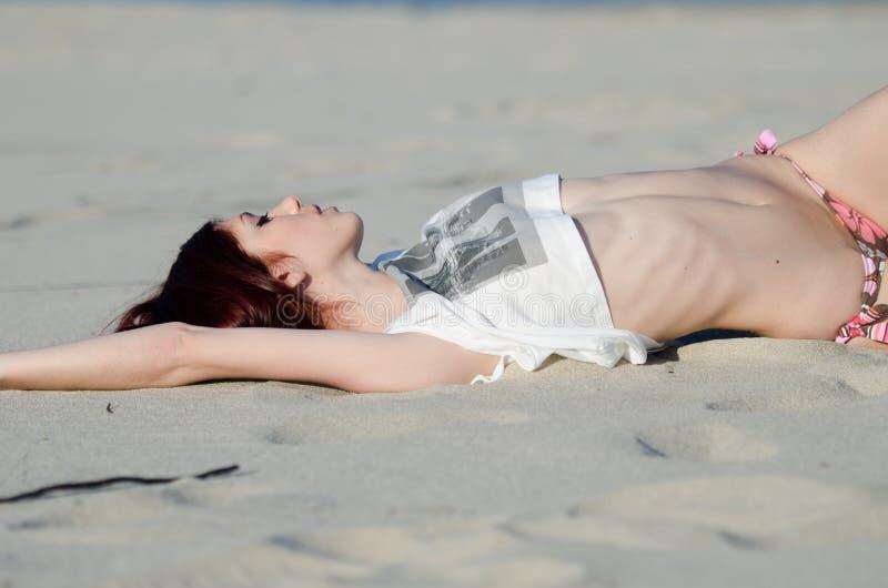Slank ung röd hårkvinna som bär den nedersta bikinin och skjortan royaltyfria bilder