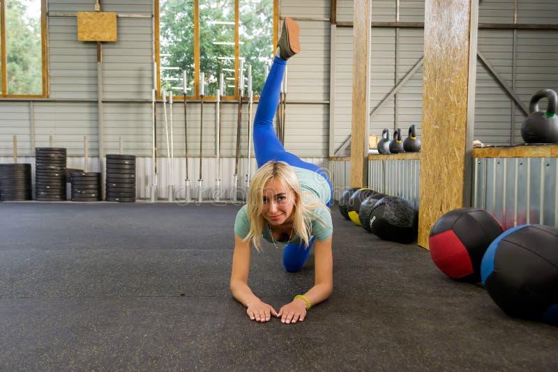 Slank ung sund sportkvinna som gör nollan för åsnasparkövning arkivbilder
