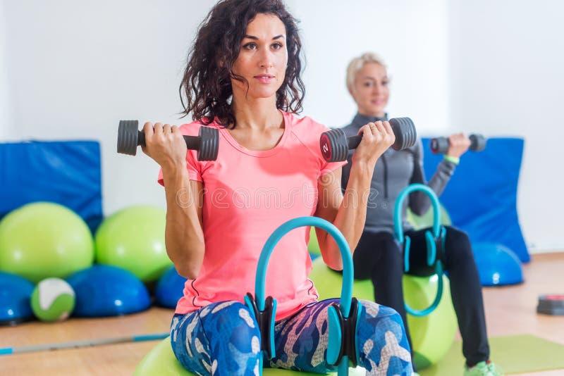 Slanka sportiga kvinnor som utbildar sammanträde på övningsbollar som rymmer hantlar och pressar den Pilates cirkeln mellan deras royaltyfri bild
