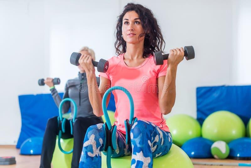 Slanka sportiga kvinnor som utbildar sammanträde på övningsbollar som rymmer hantlar och pressar den Pilates cirkeln mellan deras royaltyfri fotografi